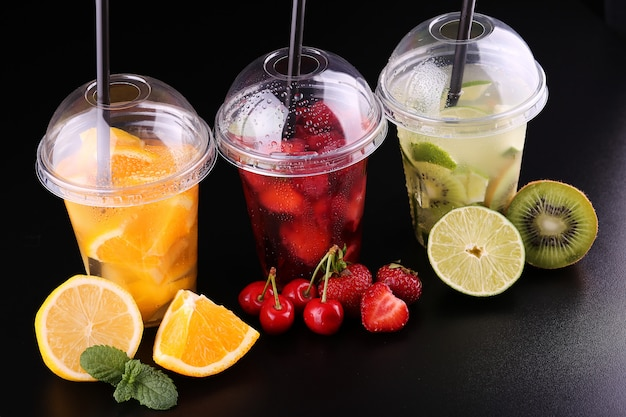 Lemonade to go. three cups with mint, cherry, strawberry, kiwi, lime, orage, lemon on black space, isolated