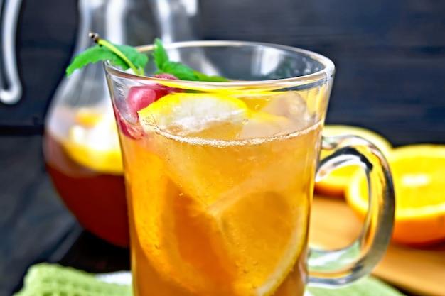 ワイングラスのレモネードとチェリー、レモン、オレンジ、木の板の背景にミントと水差し