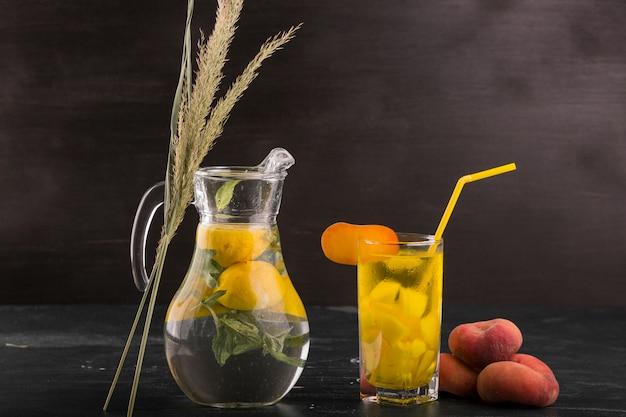 桃の周りのガラスと瓶のレモネード
