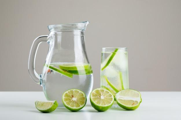 Лимонад в стакане и кувшин с лимонами, вид сбоку на белый и серый