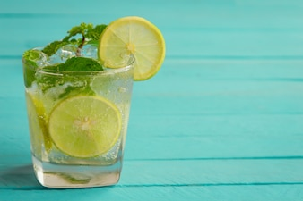 Lemonade in glass put on light blue wood table with copy space