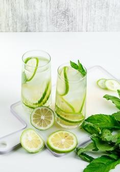 Лимонад в очках с лимоном, базиликом, разделочной доской под высоким углом зрения на белом и шероховатый