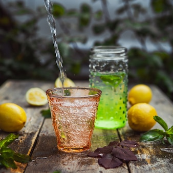 Lemonade and ingredients in glass and jar on wooden and yard table. side view.