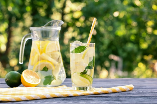 Lemonade in jug and glass and lemon with lime on wooden table