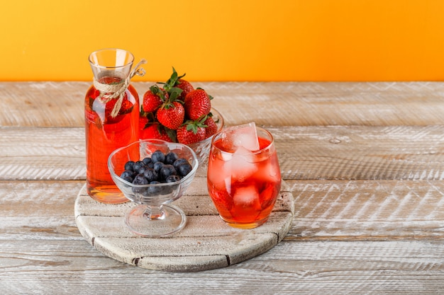 Lemonade in jug and glass with strawberries, blueberries, cutting board high angle view on orange and wooden surface