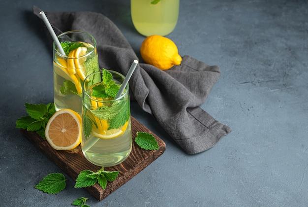 Лимонад, лимоны, мята на графитовом фоне. летний освежающий напиток. вид сбоку, копия пространства.