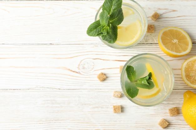 Lemonade, lemons and sugar cubes on wooden surface
