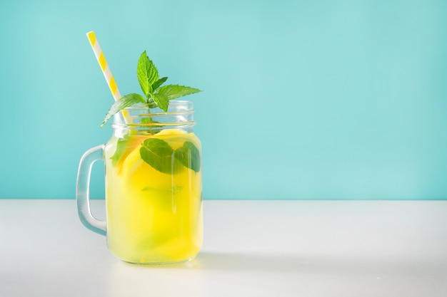 Lemonade in mason jar with lemon and mint on blue. copy space.