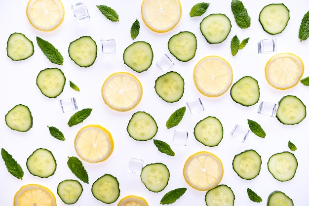Lemonade or mohito ingredients concept on white. lemon slices, mint leaves, cucumber and ice cubes.
