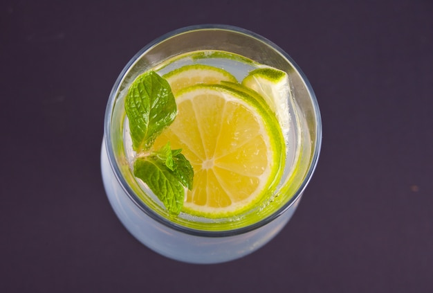 Lemonade or mojito cocktail with lemon and mint, cold refreshing drink or beverage. top view.
