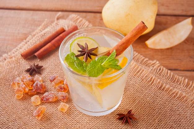 Lemonade or mojito cocktail with lemon, mint, pear and spices, cold refreshing drink or beverage.