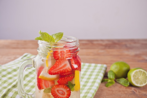 Lemonade or mojito cocktail with lemon, strawberries and mint