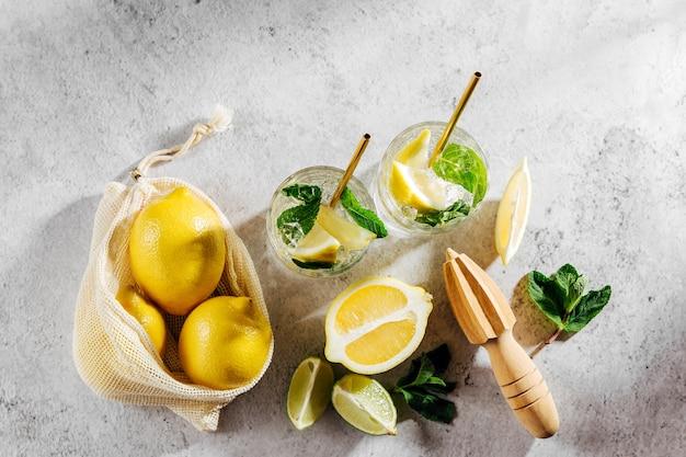 유리와 레몬에 레모네이드와 대리석 배경에 흰색 시장 가방에 라임