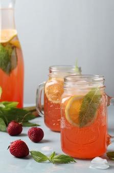 水色の表面にレモネードまたはカクテルルバーブ、イチゴ、ミント、レモン、氷