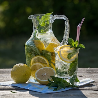 Lemonade pitcher with lemon, mint and ice, over old wooden table