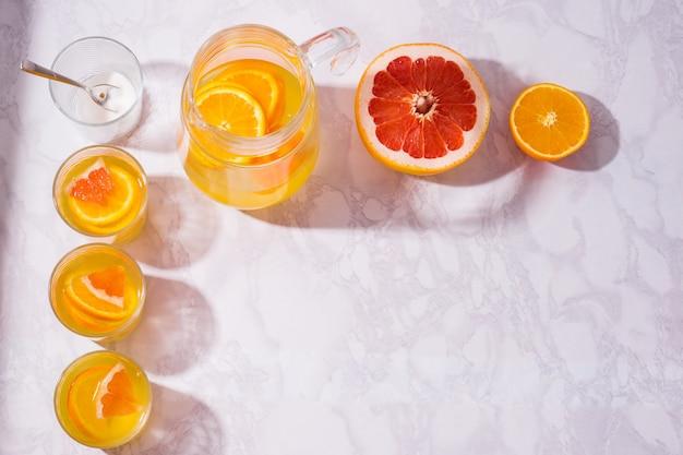 テーブルの上にオレンジ、レモン、グレープフルーツとレモネードピッチャー。白いテーブルの上に俯瞰から撮影したレモネードのグラス。