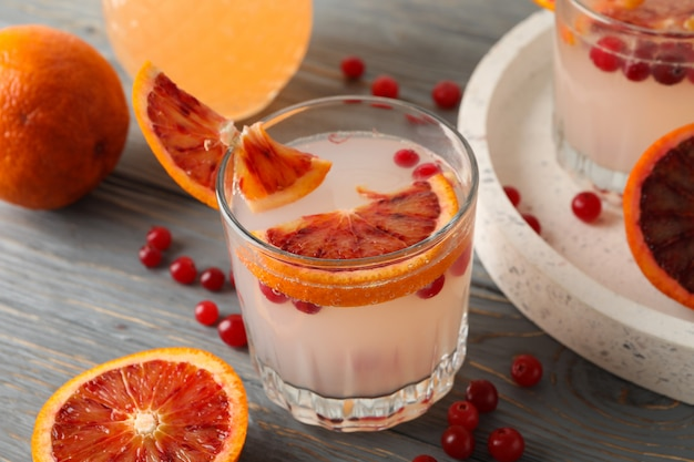 Lemonade, red orange and cranberry on wooden surface
