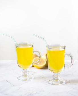 Lemonade refreshing drink in a glass beaker on a light background