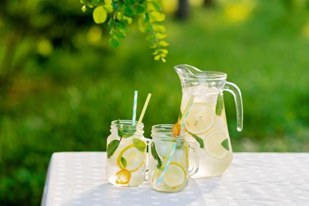 Лимонад освежающий напиток в кувшине и банки с лимонами, свежей мятой и льдом на садовом столе. летний пикник на природе. копировать пространство мягкий выборочный фокус.