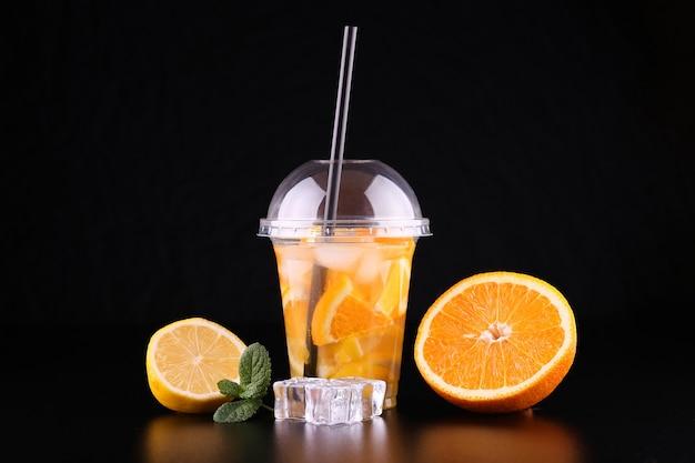 分離された黒のスペースにミント、オレンジ、レモンとカップに行くレモネード