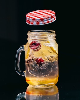 Lemonade with berries in a glass jar with open can.