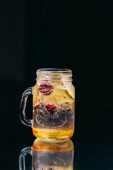 Lemonade with berries inside glass jar in a black space.
