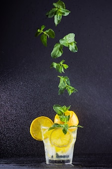 Lemonade with flying mint and lemon. summer refreshing drink with lemon on dark background. infused water with citrus and mint. summer cocktail in a spray of water. levitation
