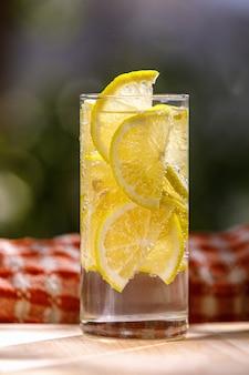 Лимонад со свежим лимоном в стекле в саду