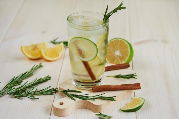Лимонад со свежим лимоном, лаймом, украшенный веточкой розмарина на светлом деревянном фоне