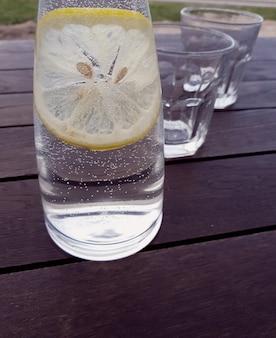 나무 배경에 신선한 레몬을 넣은 레모네이드