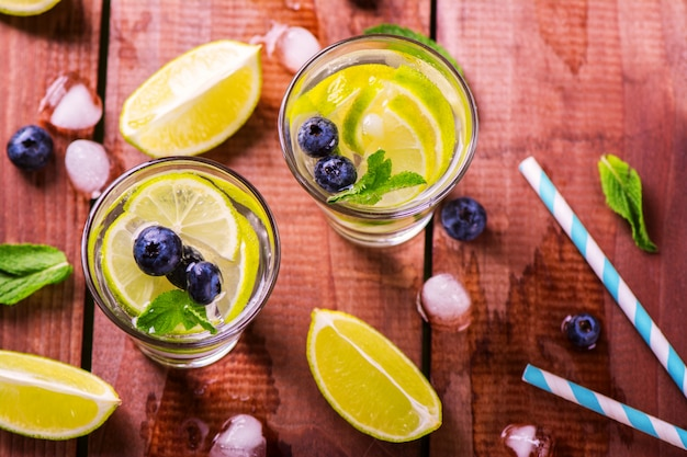Lemonade with fresh lime, berries and mint on wooden background