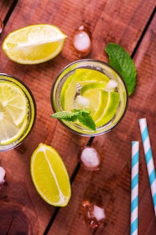 Lemonade with fresh lime and mint on wooden background