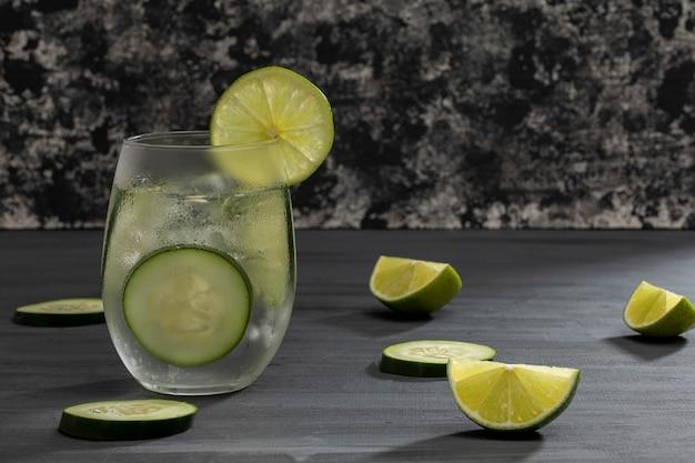 Лимонад со льдом и минеральной водой с ломтиками огурца и лимонами на сером винтажном столе