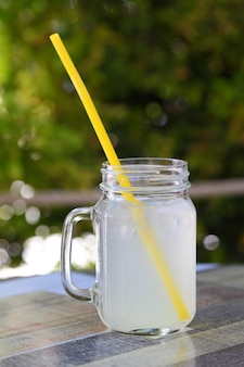 Lemonade with ice in a jar with a handle and a straw on the table with a tablecloth.