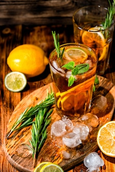 Lemonade with ice and mint on old wooden boards. ice tea with lemon and lime on a wooden table, close up.