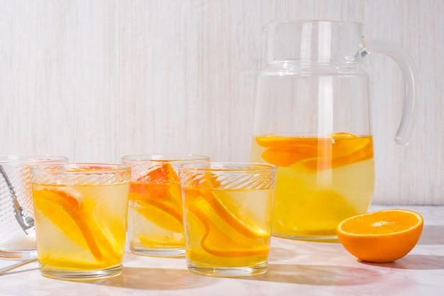 白い背景の上のガラスのレモンとグレープフルーツとレモネード。寒い夏のさわやかな飲み物や飲み物