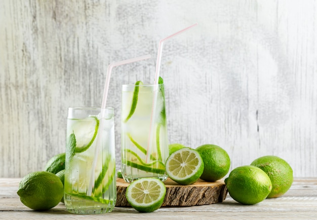 Lemonade with lemon, basil, cutting board in glasses on wooden and grungy,