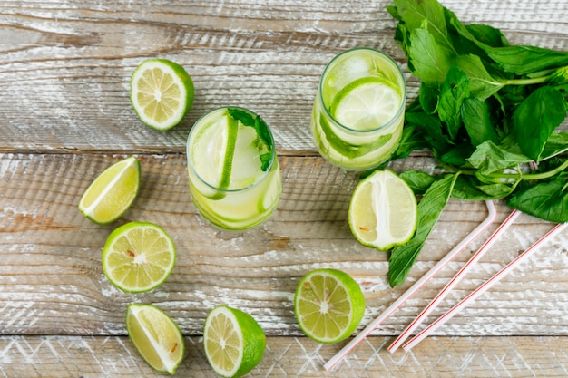 Lemonade with lemon, basil, straws in glasses on wooden, flat lay.
