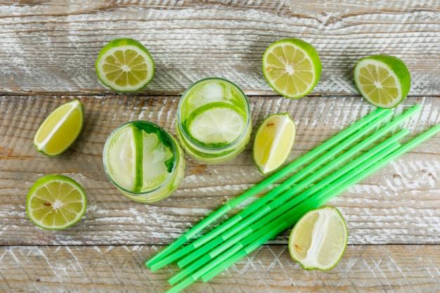 Lemonade with lemon, basil, straws in glasses on wooden, top view.