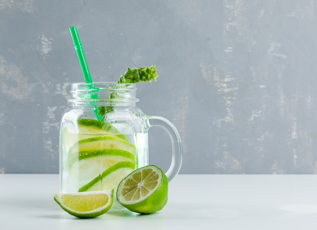 Lemonade with lemon, herbs in a mason jar glass on white and plaster,