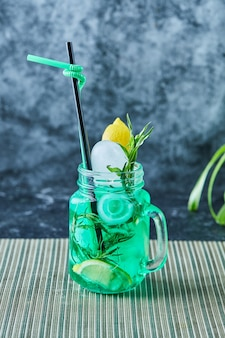 Lemonade with lemon, ice , straw and mint in the dark surface