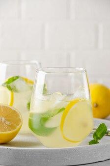 金属ストローとグラスにレモン、ミント、氷とレモネード