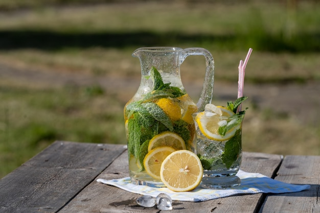 Lemonade with lemon, mint and ice, in a jug and a jar, over old wooden table, outdoor.
