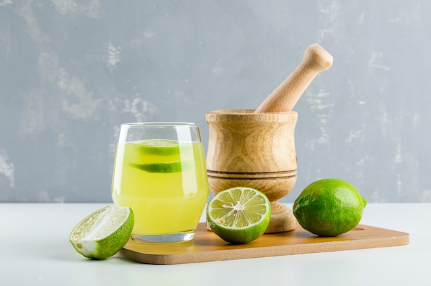 Lemonade with lemon, mortar and pestle, cutting board in a glass on white and plaster,