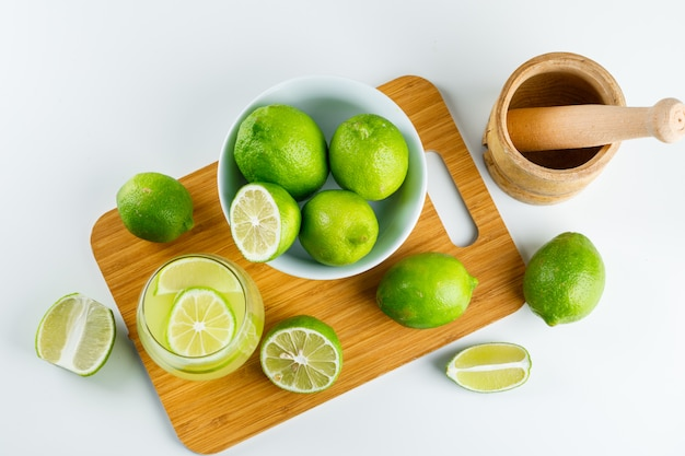 Lemonade with lemon, mortar and pestle in a glass on white and cutting board, flat lay.