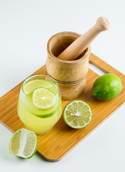 Lemonade with lemon, mortar and pestle in a glass on white and cutting board, high angle view.