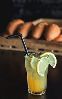 Lemonade with lemon and syrup on freshly baked rolls in the cafe. summer drink