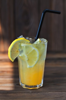 Lemonade with lemon and syrup on a wooden table. summer drink