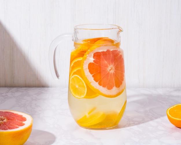 白い背景の上のガラスの瓶にレモンとグレープフルーツとレモネード。寒い夏のさわやかな飲み物や飲み物