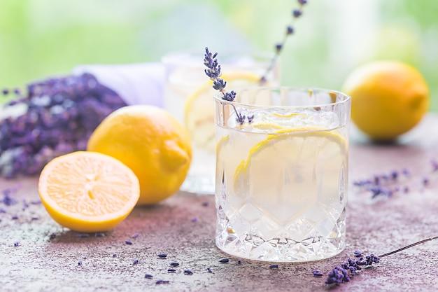 Лимонад с лимонами и лавандой на каменном столе над природой